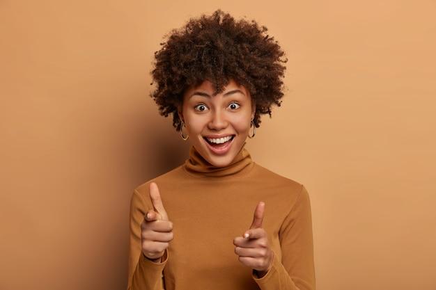확인 해봐. 행복 한 곱슬 여자는 손가락 총 제스처를 만들고, 친구를 환영하고, 누군가를 선택하고, 베이지 색 벽에 고립 된 캐주얼 터틀넥을 입은 넓은 만족스러운 미소를 가지고 있습니다. 당신은 우리에게 필요한 것입니다