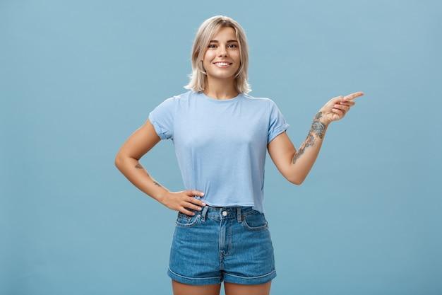 見てみな。ブロンドの髪が右を向いて、腰に手をつないで、自信を持ってリラックスしたポーズで広く笑っている美しい自信を持って若い白人の女の子の肖像画