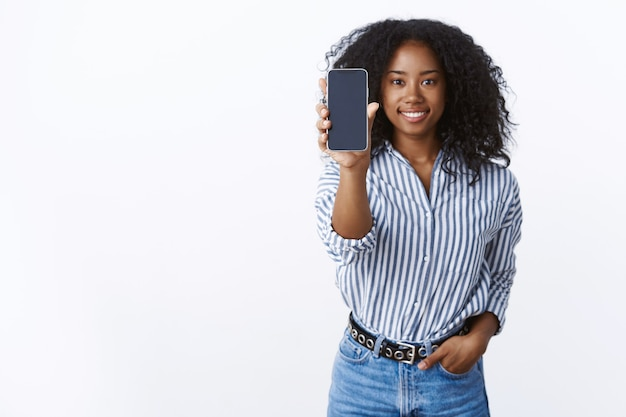 Check it out. portrait pleasant carefree charming dark-skinned smiling happy woman afro hairstyle extend arm showing you smartphone display grinning waiting your opinion, presenting app