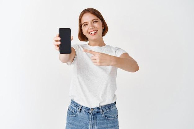 확인 해봐. 캐주얼 복장을 한 미소 짓는 아름다운 여성, 빈 스마트폰 화면을 가리키며 온라인 상점 또는 응용 프로그램, 흰색 벽을 보여줍니다.