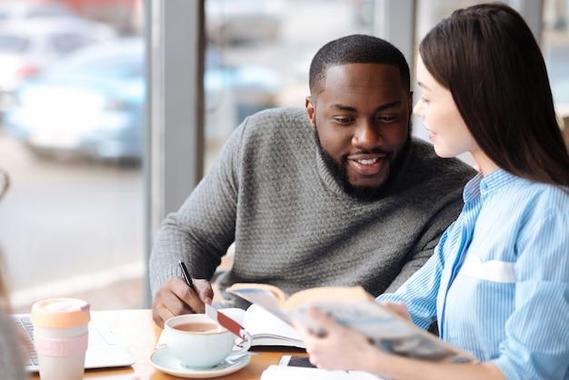 Проверь это. приятная молодая женщина, держащая книгу и показывающая несколько страниц своему другу мужского пола, сидя в кафетерии.