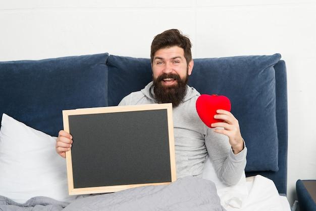 バレンタインのチェックリスト。休日のお祝い。幸せな朝。ひげを生やしたヒップスターには愛が必要です。愛の欠如。男はベッドをリラックスします。パートナーを探しています。愛の関係。バレンタインデーのコピースペース情報。