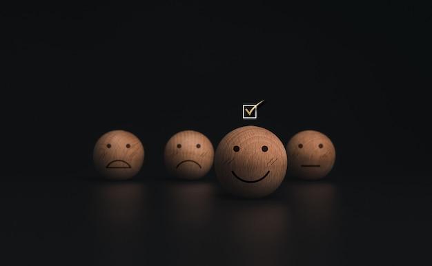 어두운 배경에 있는 나무 공의 웃는 이모티콘 얼굴에 확인란을 선택합니다. 고객 서비스 평가, 평가, 피드백 및 만족도 조사 개념.