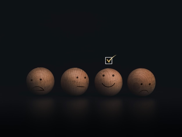 Check mark a checkbox on smiley emoticon face on the wooden balls on dark background. customer service evaluation, rating, feedback, and satisfaction survey concept.