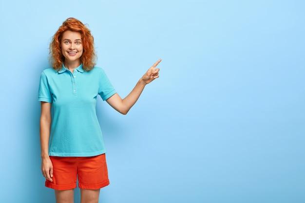Посмотри, как здорово. рыжая женщина указывает указательным пальцем в правом верхнем углу