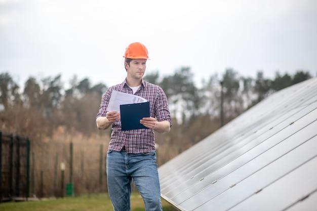 Проверка, особый объект. молодой взрослый серьезный человек в защитном шлеме с папкой возле инженерного объекта на открытом воздухе в течение дня