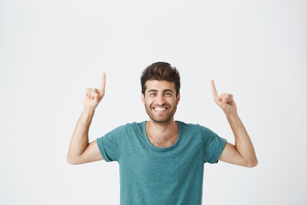 Check this out cropped  shot of attractive good-looking excited young man in blue t-shirt pointing fingers up having surprised look, with cheerful and happy expression of face. broadley smiling