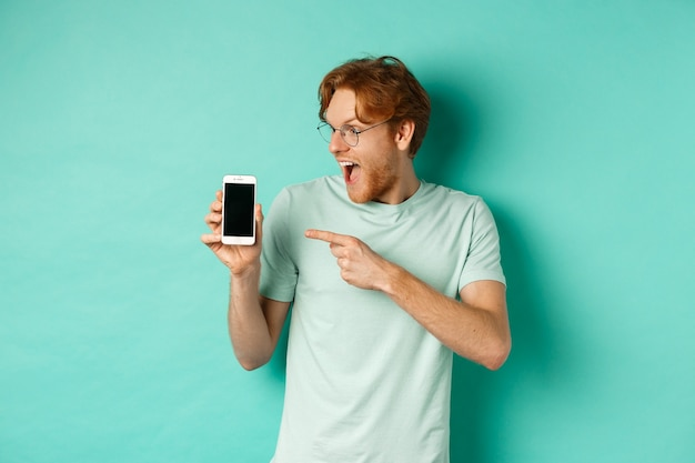 Check this out. handsome redhead guy in glasses pointing finger at blank smartphone screen, showing online promotion, standing amazed over turquoise background.