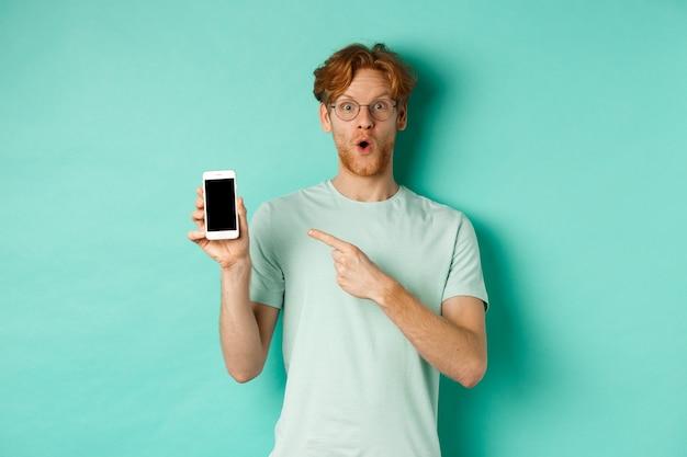 これをチェックしてください。空白のスマートフォンの画面に指を指して、オンラインプロモーションを表示し、ターコイズブルーの背景に驚いて立っている眼鏡のハンサムな赤毛の男