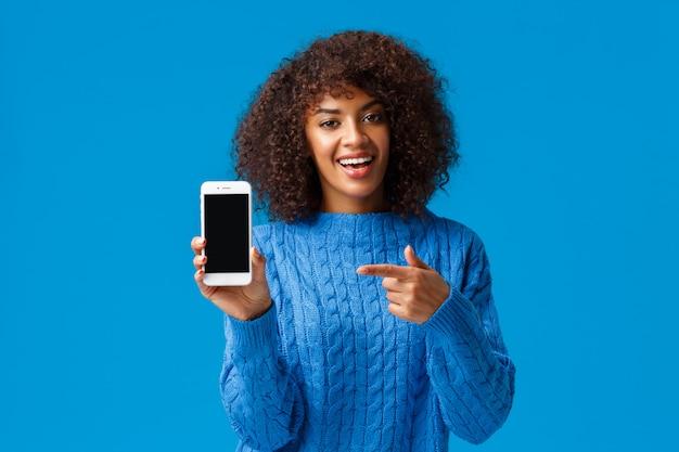 これをチェックしてください。幸せなカリスマ的なアフリカ系アメリカ人の女性、アフロのヘアカット、スマートフォンを保持、モバイル画面を表示、アプリケーション、ショッピングアプリ、またはゲームのプロモーションとしてディスプレイを指す