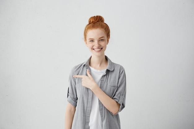 これをチェックしてください。生姜の髪が明るく笑って、離れて指を指す、空白の壁にコピースペースを示す、うれしそうな幸せそうな表情を持つ魅力的な肯定的な若い女性の肖像画
