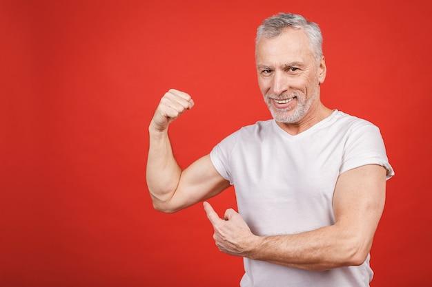 Проверь это! старший мужчина, показаны мышцы. постаретый человек сгибая его изолированные руки. веселый возбужденный современный крутой пенсионер дедушка практикует бодибилдинг.