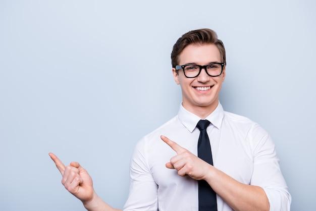 これをチェックしてください!純粋な水色のスペースで若い陽気な成功した弁護士は笑顔で、フォーマルな服を着て、彼の指でコピースペースを指しています