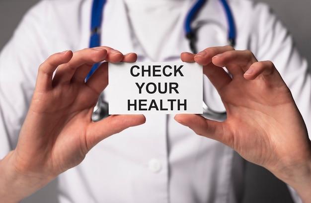 医師の手で紙にあなたの健康碑文を確認してください