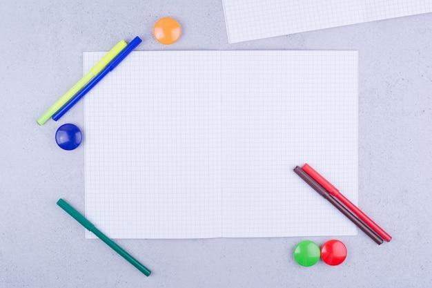 Un foglio bianco controllato con penne e spilli intorno