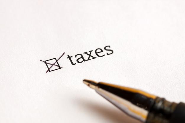 Проверенный флажок с налогами и долларами слова на предпосылке. концепция анкеты.