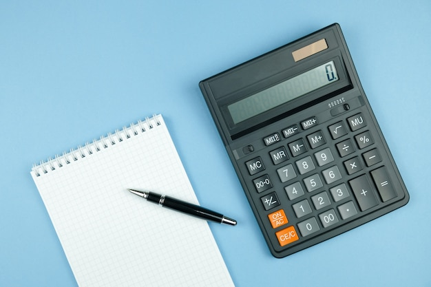 Проверенная тетрадь с белой бумагой и ручкой, черным большим калькулятором на голубой предпосылке.