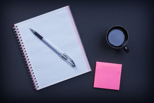 Checked notepad pen sticky note and cup of coffee on black wall education concept