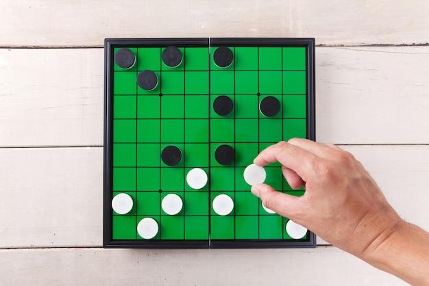 Checker игра на зеленой доске вид сверху на деревянный стол.