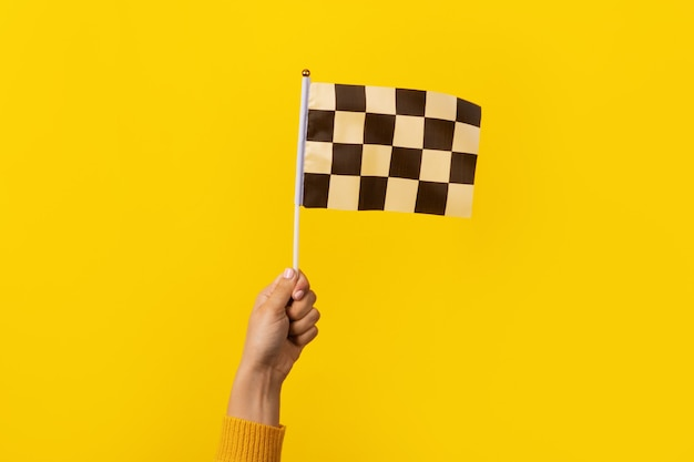 Checkered flag in hand over yellow background