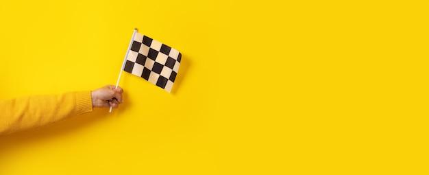 黄色の背景、パノラマ画像の上に手にチェッカーフラッグ