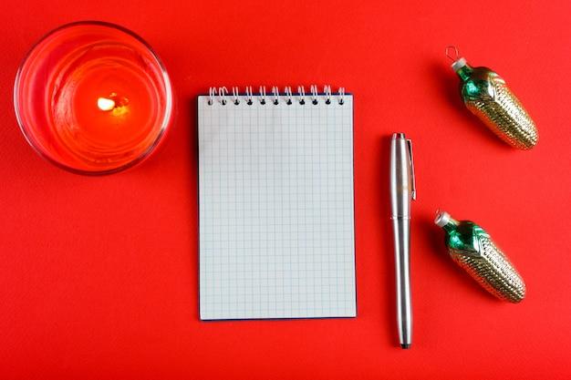 Клетчатый блокнот, ручка с двумя шишками, свеча на красном новогоднем фоне.