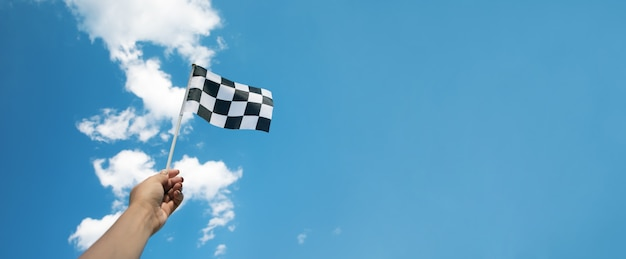 Checkered race flag in hand over blue sky