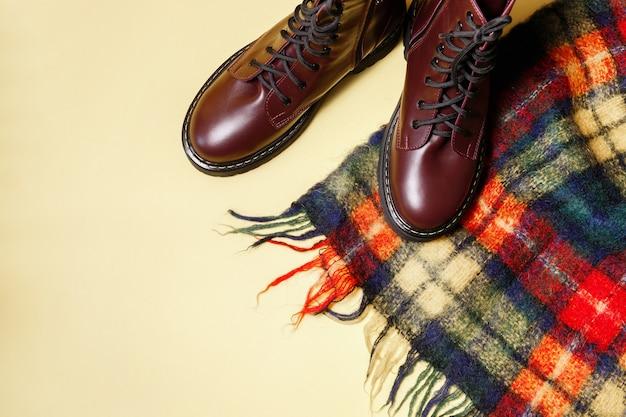 黄色の秋の背景に市松模様のスカーフと秋のブーツ
