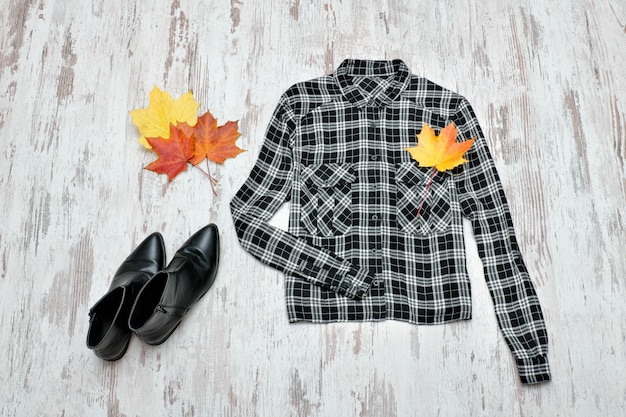 Checkered shirt, black shoes and maple leaves. fashionable concept