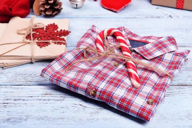 흰색 나무 배경에 크리스마스 선물이 있는 체크 무늬 셔츠, 클로즈업