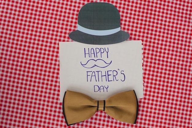 Superficie a scacchi con fiocco di arco e cappello per la giornata del padre