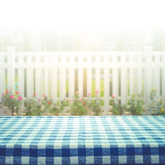 Checkered tablecloth on blur of white fence and garden background.