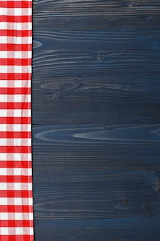Checkered tablecloth on wooden table background