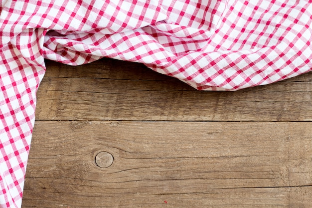 Checkered tablecloth on wooden table top view