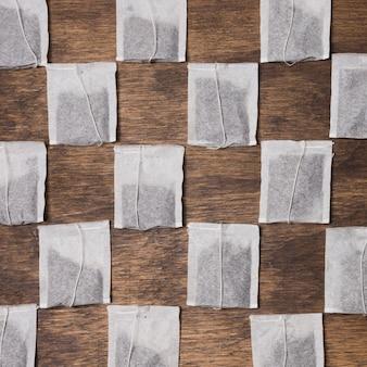 木製の織り目加工の背景に市松模様のティーバッグ