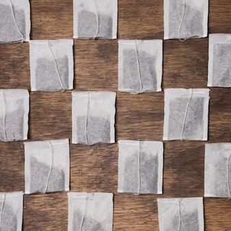 Checkered tea bag on wooden textured background