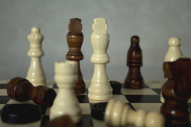 Шашки и шахматные фигуры на шахматной доске крупным планом