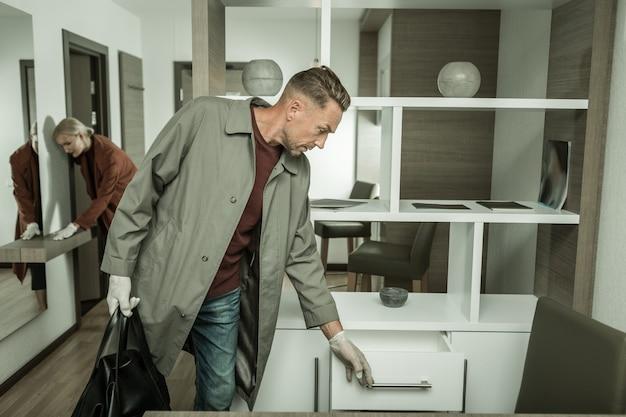 모든 표면을 확인합니다. 직장 동료가 장갑으로 표면을 만지는 동안 증거를 찾고있는 사물함을 여는 매력적인 수사관