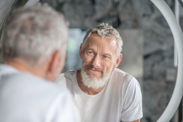 Checking an appearance. a grey-haired man looking at his reflection in the mirror