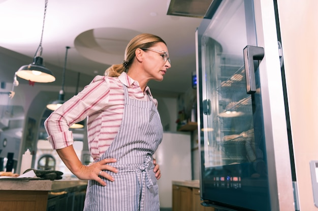 利用可能かチェックしている。デザートの入手可能性をチェックするパン屋のブロンドの髪の勤勉な労働者
