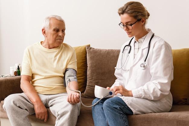 Проверка артериального давления. молодая женщина-врач и пожилой мужчина.