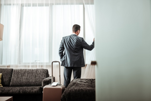 도시 전망을 확인 중입니다. 그의 호텔 방에서 도시 전망을 확인하는 검은 머리 성공적인 사업가