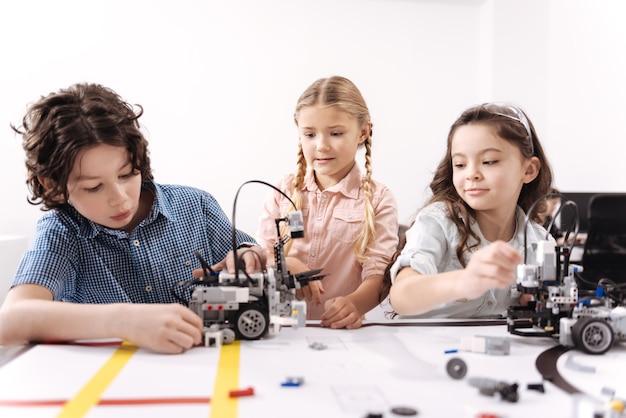 制御システムをチェックしています。クラスに座って、技術プロジェクトに取り組んでいる間ロボットを使用している有能な創造的な独創的な子供たち