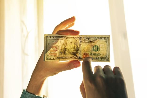 偽金の光をチェックしています。彼の手にある窓に対して100ドル。新しい百ドル札の透かしを確認してください。アメリカ通貨の半透明。