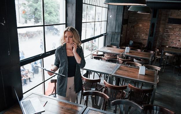 データをチェックしています。昼間のカフェで室内に金髪の巻き毛を持つ実業家。