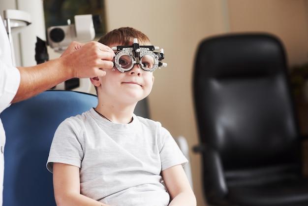 別のレンズをチェックしています。医院に座って視力をテストした子供。