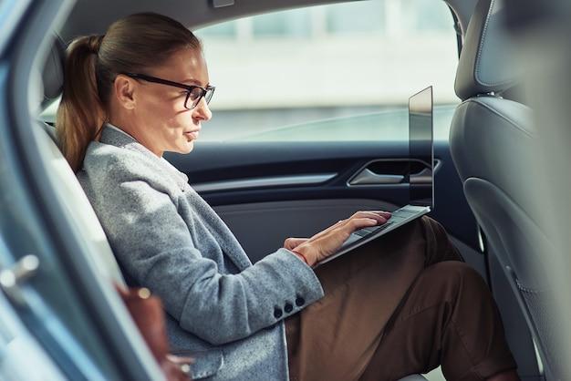 Проверка электронной почты, вид сбоку сосредоточенной бизнес-леди средних лет, использующей ноутбук, сидя на спине