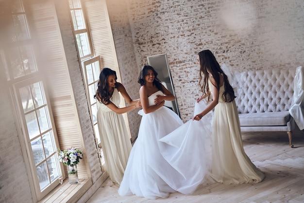 Проверяем каждую деталь. вид сверху в полный рост двух привлекательных молодых женщин, поправляющих свадебное платье на невесте, стоя у окна вместе