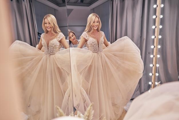 모든 세부 사항을 확인합니다. 피팅 룸에 서 있는 동안 신부에 웨딩 드레스를 조정 하는 매력적인 젊은 여자의 반영