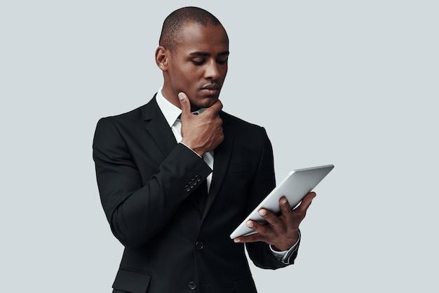 모든 세부 사항을 확인합니다. 회색 배경에 서 있는 동안 디지털 태블릿을 사용하여 작업하는 정장 차림의 젊은 아프리카 남자